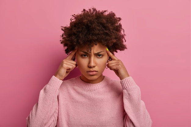 진지한 강렬한 아프리카 계 미국인 여성은 작업에 집중하고 깊이 생각하며 사원에 검지 손가락을 유지하고 두통이나 편두통으로 고통 받고 우울한 표정으로 보이며 캐주얼 점퍼를 입습니다.