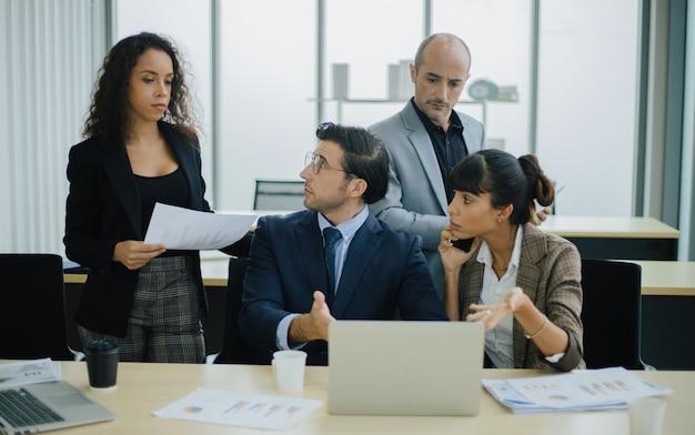 Серьезные международные разноплановые деловые люди обсуждают обзор финансовых результатов с ноутбуком.