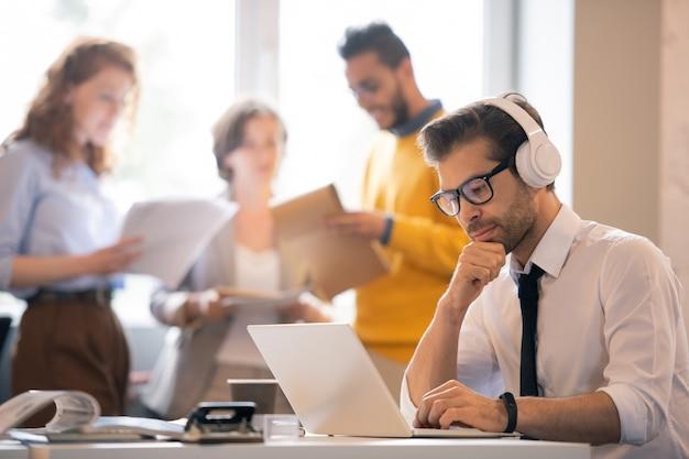 テーブルに座ってラップトップでオンラインドキュメントを読むヘッドフォンで深刻な内省的な男性マネージャー