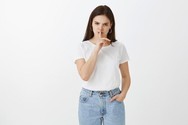 Серьезная раздраженная молодая женщина позирует у белой стены