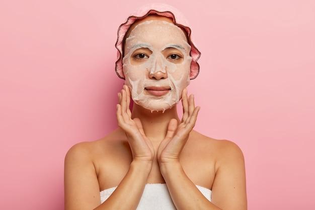 진지한 일본 여성은 얼굴에 영양 마스크를 쓰고 피부에 보습 시트 제품을 바르고 목욕 모자를 쓰고 분홍색 벽에 포즈를 취합니다. 여성, 미용 및 스파 트리트먼트 개념