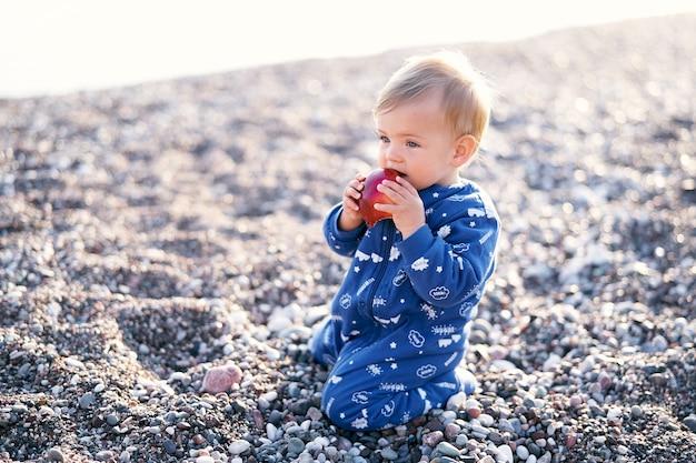 파란색 바지를 입은 심각한 아이가 조약돌 해변에 무릎을 꿇고 사과를 갉아 먹는다.