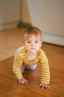 Serious kid is on all fours on the wooden floor in the kitchen closeup