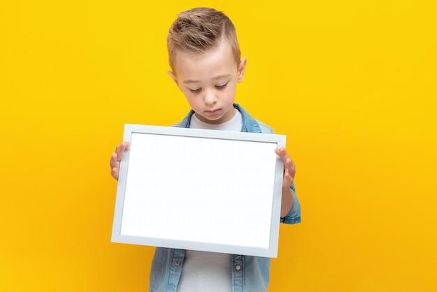 Серьезный ребенок смотрит на белую рамку в руках с копией пространства для текста сертификата или диплома