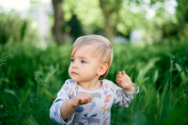 Serious kid sits in the tall grass portrait