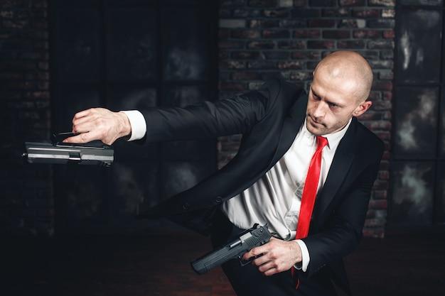 深刻なキラーが両手で拳銃を撃つ