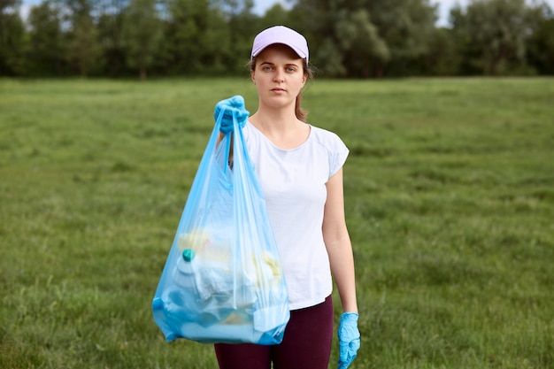 Serious lady in baseball cap holding garbage bag full of trash in hands, showing it to people
