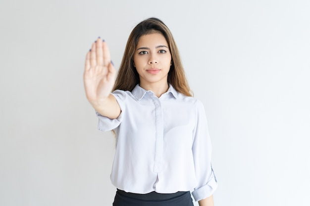 Serious lady showing open palm or stop gesture