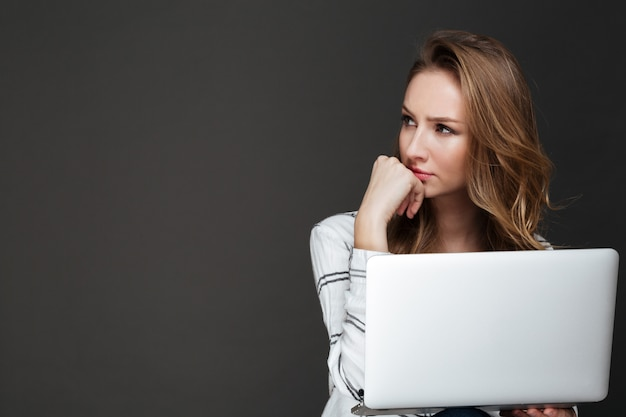 Serious lady using laptop over dark wall