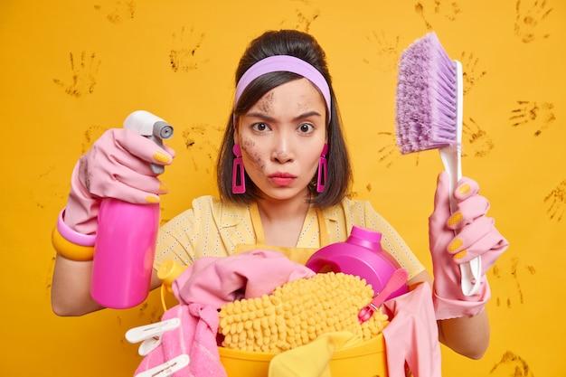 汚れた顔の真面目な女性がカメラを注意深く見ていますブラシスプレー洗剤はヘッドバンドを身に着けていますエプロンは黄色の壁の上に隔離された洗濯かごの近くに立っています