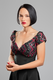 Serious lady with short dark hair and red lips posing in studio