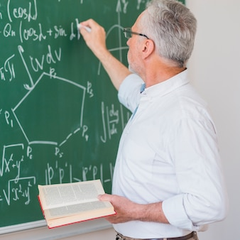 Serious lecturer in glasses chalking formula on blackboard