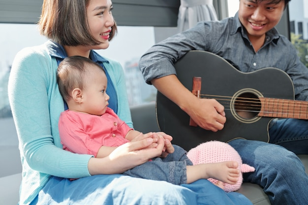 Serious little baby girl sitting on laps of her mom and lookng at her dad playing guitar and singing