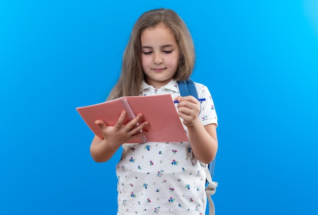 Serious little beautiful girl with long hair with backpack holding notebook looking at it writing something with pen standing on blue