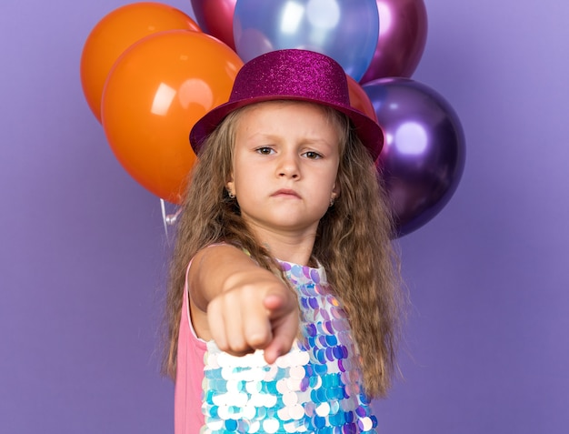Serious little blonde girl with violet party hat pointing  standing in front of helium balloons isolated on purple wall with copy space