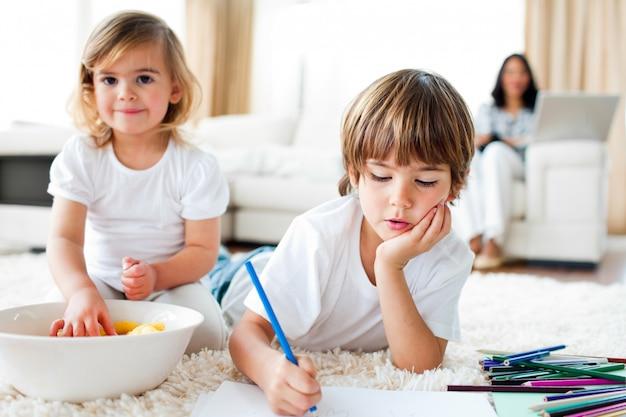 深刻な小さな男の子の描画と彼の妹のチップを食べる