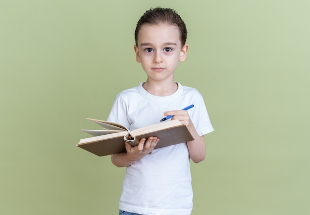 Serious little boy looking at camera holding book and pen isolated on olive green wall with copy space