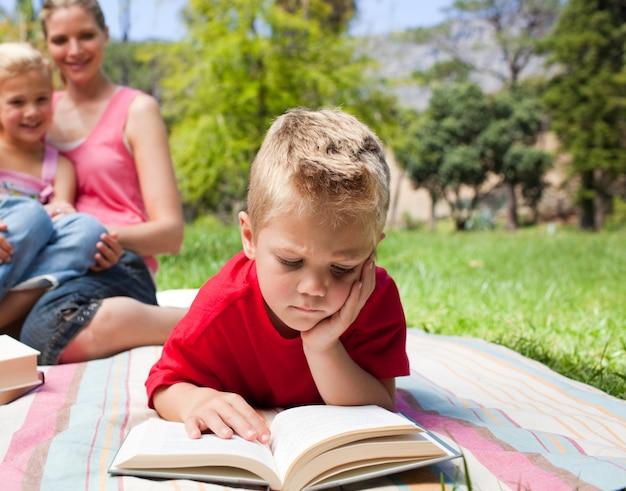 家族と一緒にピクニックをしている間に読書をしている少年