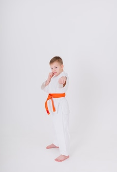 Serious little boy in a white kimono with an orange belt stands at full height in a pose on a white wall