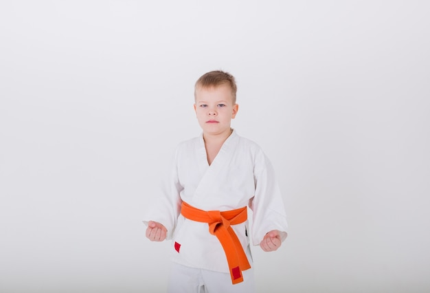 Serious little boy in a white kimono with an orange belt stands in a pose against a white wall with a copy of the space