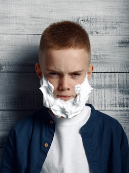 Serious little boy with shaving foam on his face in studio. kid isolated on wooden background, child emotion, schoolboy photo session