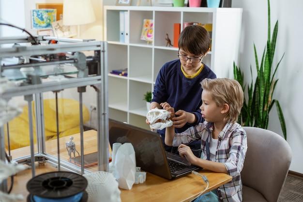 노트북이 장착 된 실험실에 앉아 3d 프린터에서 모델을 관찰하는 심각한 작은 소년