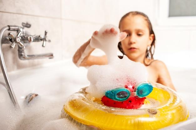 진지한 작은 귀여운 소녀는 거품 목욕에 목욕하고 바다에 자신을 상상하는 장난감을 가지고 노는. 바다에서 여름 휴가의 어린이 꿈의 개념