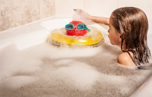 진지하고 귀여운 소녀가 거품 목욕을 하고 바다에 자신을 상상하는 장난감을 가지고 노는 것입니다. 바다에서 여름 휴가를 꿈꾸는 아이들의 개념