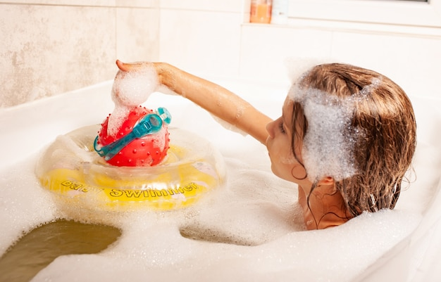 심각한 귀여운 소녀는 거품 목욕에 목욕하고 장난감을 가지고 노는