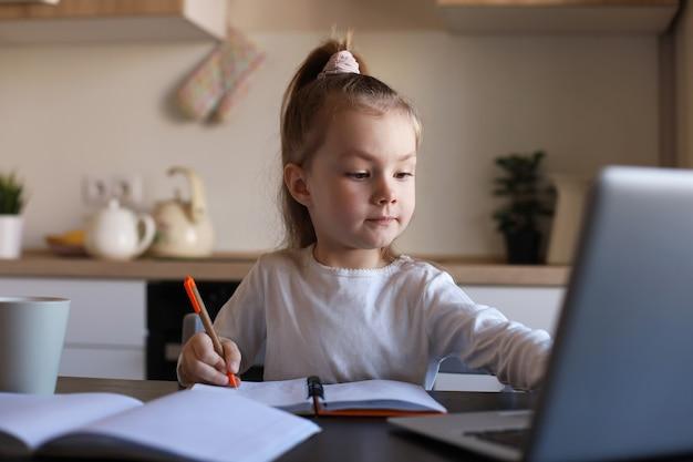 집에서 노트북을 사용하여 온라인으로 공부하는 진지한 어린 소녀, 귀여운 행복한 어린 아이가 인터넷 웹 수업이나 컴퓨터 수업, 홈스쿨링 개념