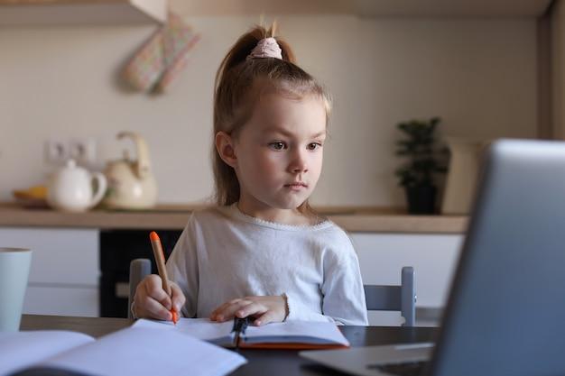 진지한 어린 소녀는 집에서 노트북을 사용하여 온라인으로 필기 공부를 하고, 귀엽고 행복한 어린 아이는 pc에서 인터넷 웹 수업이나 수업을 받습니다.