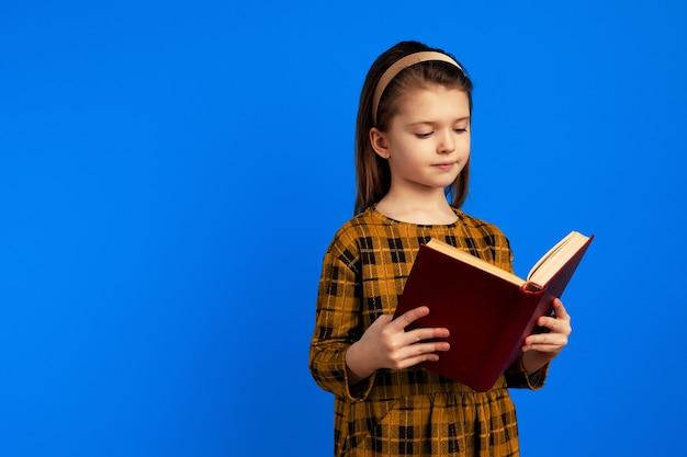 Серьезная маленькая девочка, читающая книгу, стоя на синем фоне
