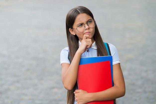 안경을 쓴 진지한 어린 아이는 야외에서 사려 깊은 표정으로 학교 책을 들고 상상력을 발휘합니다.