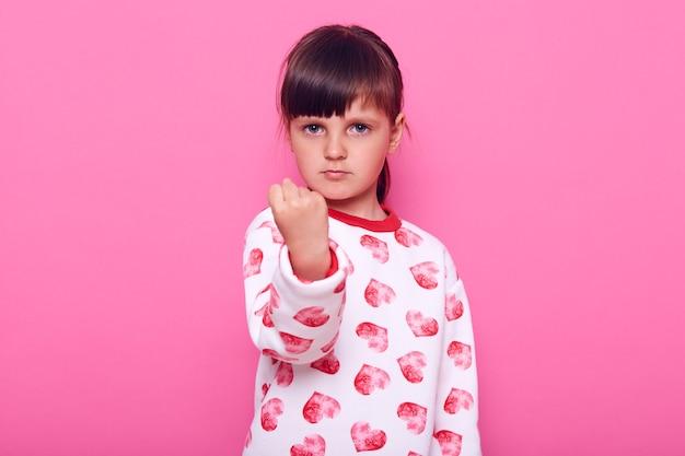 Серьезная маленькая девочка дошкольника с темными волосами в свитере, смотрящая в камеру с сердитым выражением лица и показывающая кулак, изолирована над розовой стеной.