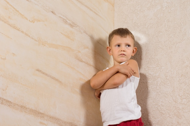 Serious little white kid wearing undershirt isolated on wooden walls