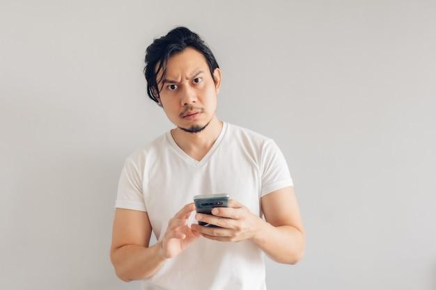 白いカジュアルなtシャツを着た真面目な長髪の男性がスマートフォンを使用しています。
