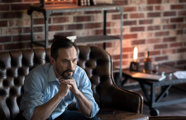 真面目な表情。彼のあごを保持し、ソファに座っている間思慮深く見ている魅力的な思慮深いスタイリッシュな男