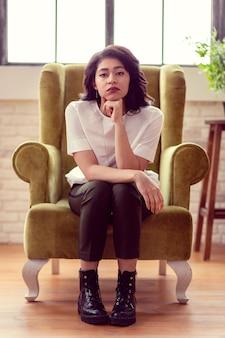 진지한 표정. 안락의 자에 앉아있는 동안 당신을 찾고 아름 다운 검은 머리 여자
