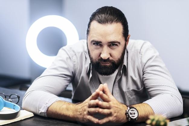 真面目な表情。焦点を合わせているように見える彼の手に大きな時計を身に着けている黒髪のひげを生やした男