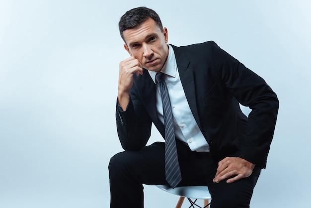 真面目な表情。あなたを見て、椅子に座って彼の人生について考えている素敵な楽しいハンサムな起業家