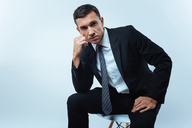 Serious look. nice pleasant handsome entrepreneur looking at you and thinking about his life while sitting on the chair