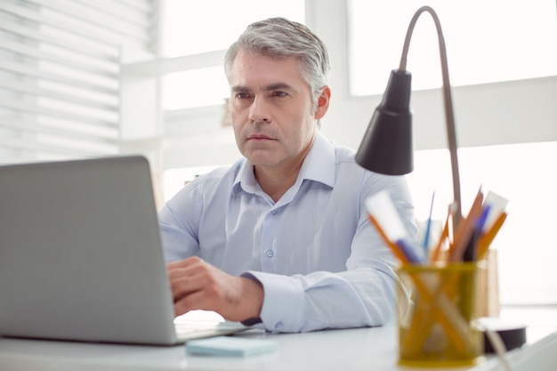 真面目な表情。テーブルに座って、作業中にノートパソコンの画面を見ているスマートな素敵な自信のある男