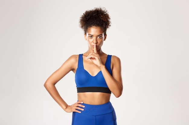 Serious-looking african-american fitness woman shushing at camera, telling to keep quiet, standing
