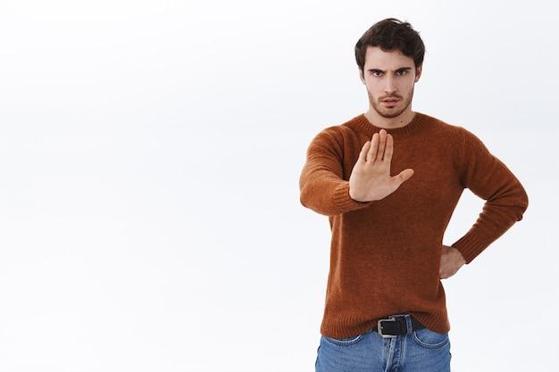 캐주얼 복장을 한 진지하고 자신감 있는 젊고 강한 미남이 손을 앞으로 당겨 중지 제스처를 보여줍니다.