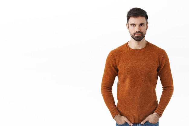 Serious-looking assertive bearded man, family guy in sweatshirt, hold hands in pockets determined with pleased, confident smile, standing white wall on right side