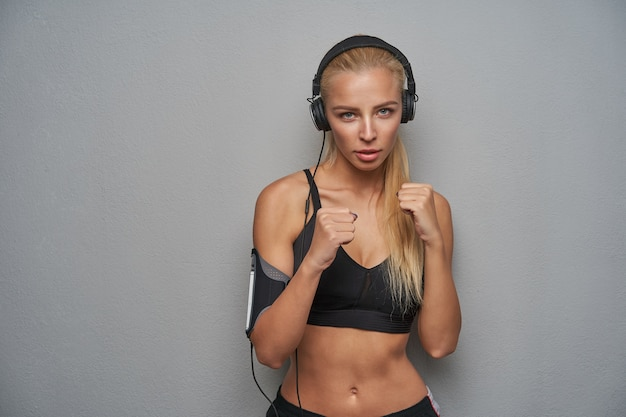 Serious looking attractive slim blonde lady with casual hairstyle posing over light grey background in defensive position, raising fists and being ready to fight