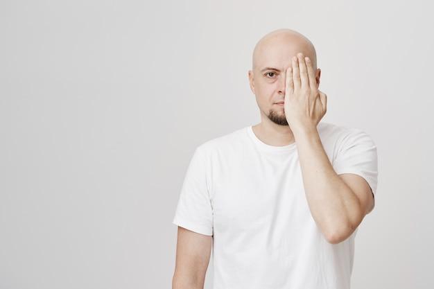심각한 표정의 대머리 남자가 손으로 얼굴의 절반을 덮습니다.