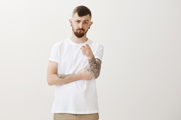 Uomo barbuto dall'aspetto serio che punta il dito davanti con accusa