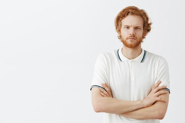 白い壁に向かってポーズをとっている真面目なひげを生やした赤毛の男