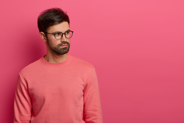 진지하게 보이는 수염을 가진 성공적인 남성 직원은 오른쪽에 집중하고 미래의 작업 문제에 대해 깊은 생각을 가지고 있으며 투명한 안경과 장미 빛 점퍼를 착용하고 실내에서 포즈를 취합니다. 흑백 샷